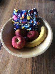 Milovia Stoffwindel Fruity in einer mit Früchten gefüllten Obstschale