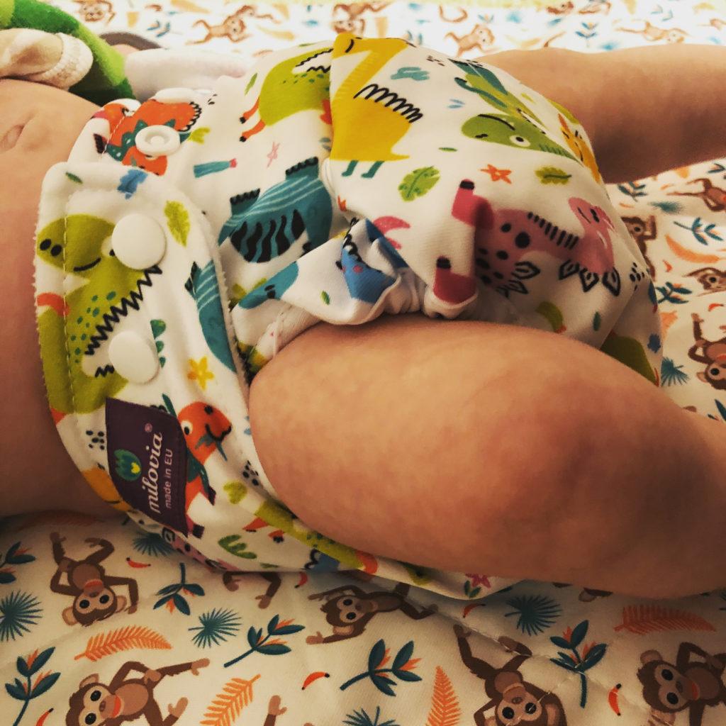 Neugeborenes Baby mit einer Milovia Stoffwindel, Modell Dinosaurier